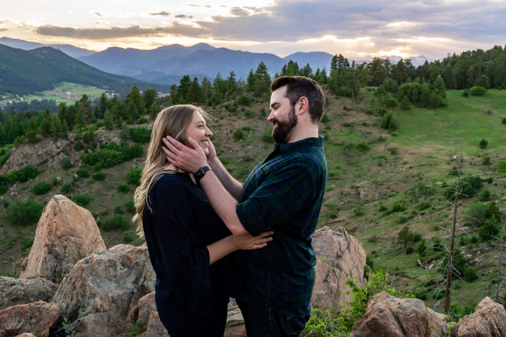 A newly engaged couple looking into each others eyes and smiling in front of the sunset. Photo by Gabby Jockers Photography. Mount falcon engagement photography, colorado engagement photos, colorado engagement session, mountain engagement photos, mountain session, colorado photography, outdoor engagement photos, outdoor engagement session, hiking engagement, adventure photos, adventure session, couples photos