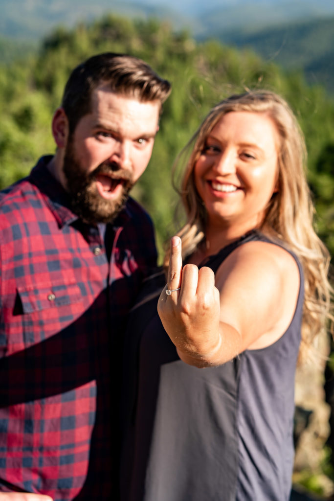 "A women ""flipping off"" the camera but with her ring finger with the man next to her making a surprised face. Photo by Gabby Jockers Photography. Mount falcon engagement photography, colorado engagement photos, colorado engagement session, mountain engagement photos, mountain session, colorado photography, outdoor engagement photos, outdoor engagement session, hiking engagement, adventure photos, adventure session, couples photos"