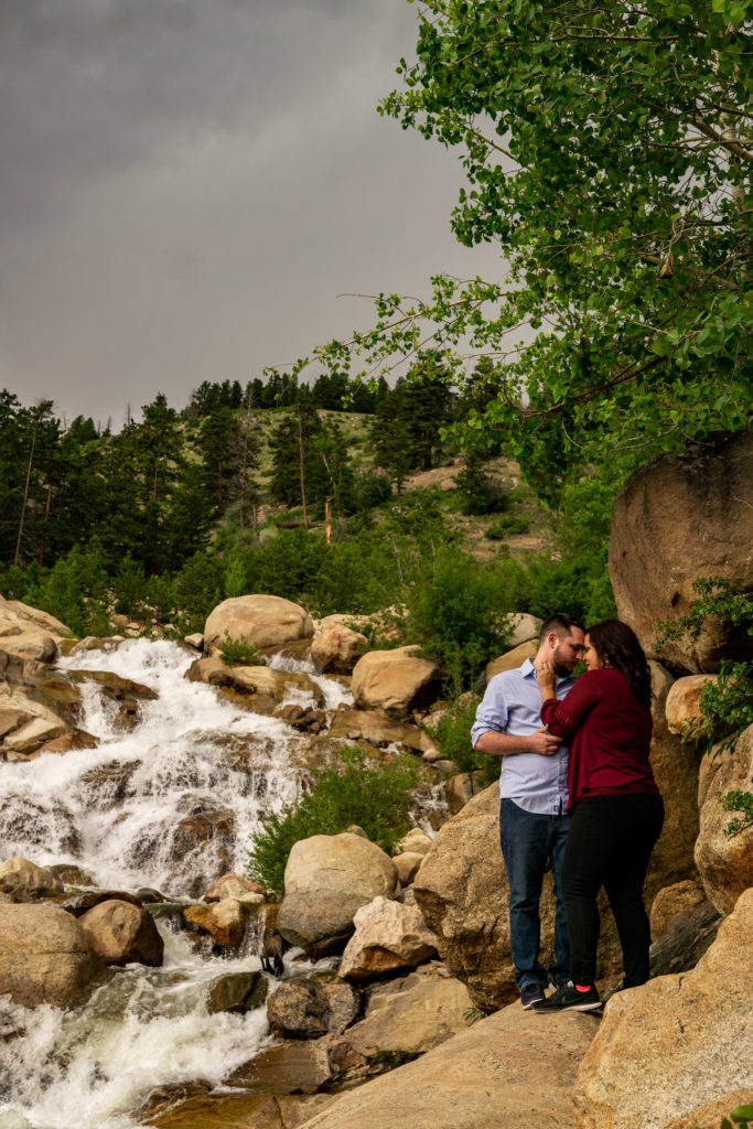 A newly engaged couple snuggling up in front of the Alluvial Fan waterfall in Rocky Mountain National Park. Photo by Gabby Jockers Photography. rmnp engagement photography, rmnp engagement photos, rmnp engagement session, rocky mountain national park engagement photos, rocky mountain national park engagement session, rocky mountain national park photography, waterfall engagement photos, dream lake engagement photos, waterfall engagement session, hiking engagement, adventure photos, adventure session, couples photos
