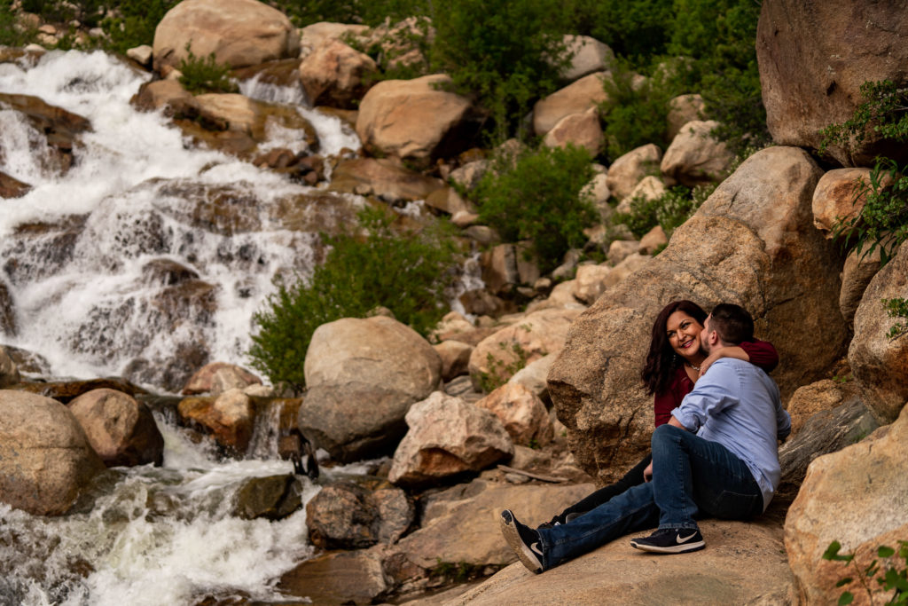 A newly engaged couple sitting and snuggling up in front of the Alluvial Fan waterfall in Rocky Mountain National Park. Photo by Gabby Jockers Photography. rmnp engagement photography, rmnp engagement photos, rmnp engagement session, rocky mountain national park engagement photos, rocky mountain national park engagement session, rocky mountain national park photography, waterfall engagement photos, dream lake engagement photos, waterfall engagement session, hiking engagement, adventure photos, adventure session, couples photos