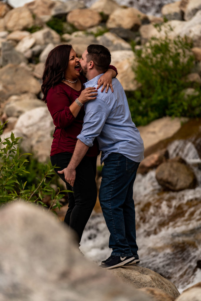 A man and woman playing on the rocks outside at the Alluvial Fan in Rocky Mountain National Park. Photo by Gabby Jockers Photography. rmnp engagement photography, rmnp engagement photos, rmnp engagement session, rocky mountain national park engagement photos, rocky mountain national park engagement session, rocky mountain national park photography, waterfall engagement photos, dream lake engagement photos, waterfall engagement session, hiking engagement, adventure photos, adventure session, couples photos