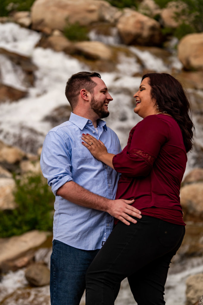 A newly engaged couple snuggling up and laughing together in front of the Alluvial Fan waterfall in Rocky Mountain National Park. Photo by Gabby Jockers Photography. rmnp engagement photography, rmnp engagement photos, rmnp engagement session, rocky mountain national park engagement photos, rocky mountain national park engagement session, rocky mountain national park photography, waterfall engagement photos, dream lake engagement photos, waterfall engagement session, hiking engagement, adventure photos, adventure session, couples photos