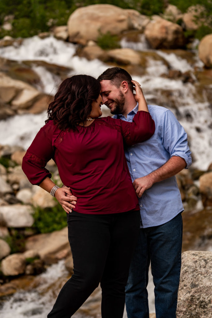 A man and woman in a passionate embrace in front of the Alluvial Fan waterfall in Rocky Mountain National Park. Photo by Gabby Jockers Photography. rmnp engagement photography, rmnp engagement photos, rmnp engagement session, rocky mountain national park engagement photos, rocky mountain national park engagement session, rocky mountain national park photography, waterfall engagement photos, dream lake engagement photos, waterfall engagement session, hiking engagement, adventure photos, adventure session, couples photos