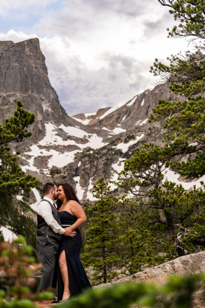 A man and woman in suit and gown smiling and kissing in front of dream lake in the national park. Photo by Gabby Jockers Photography. rmnp engagement photography, rmnp engagement photos, rmnp engagement session, rocky mountain national park engagement photos, rocky mountain national park engagement session, rocky mountain national park photography, waterfall engagement photos, dream lake engagement photos, waterfall engagement session, hiking engagement, adventure photos, adventure session, couples photos