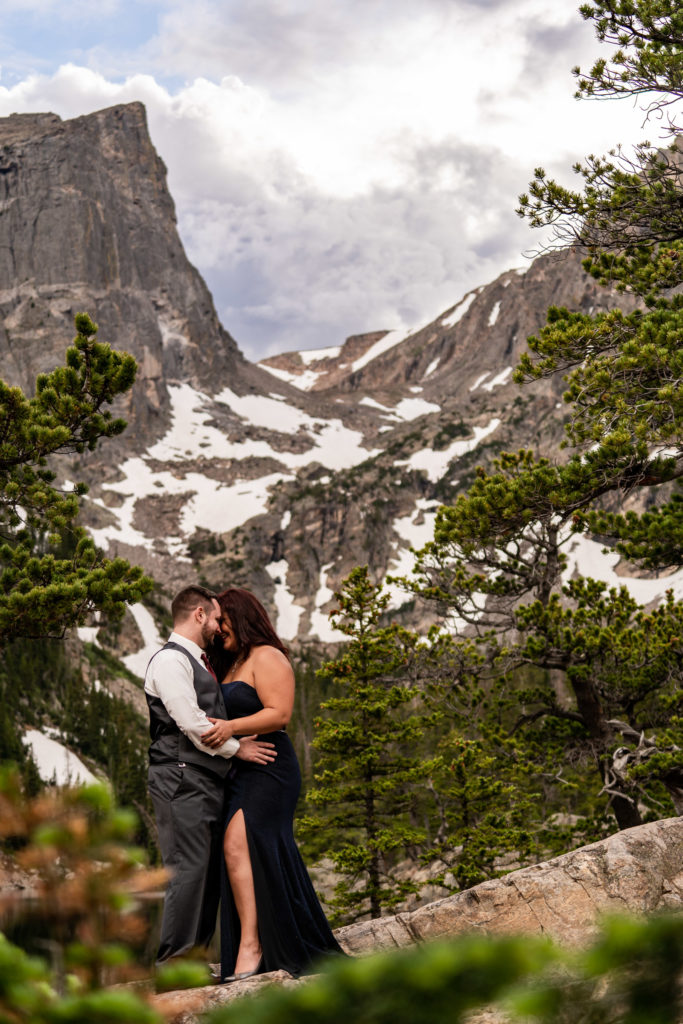 PA man and woman in suit and gown smiling and kissing in front of dream lake in the national park. hoto by Gabby Jockers Photography. rmnp engagement photography, rmnp engagement photos, rmnp engagement session, rocky mountain national park engagement photos, rocky mountain national park engagement session, rocky mountain national park photography, waterfall engagement photos, dream lake engagement photos, waterfall engagement session, hiking engagement, adventure photos, adventure session, couples photos