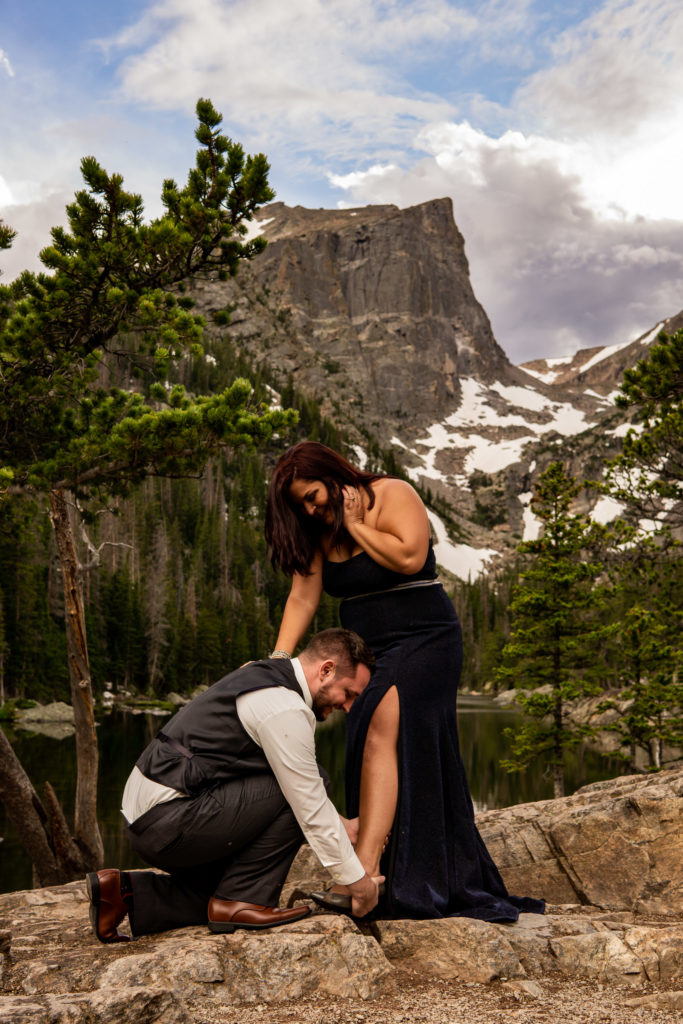 A man helps his fiance with her shoe as they stand in front of Dream Lake. Photo by Gabby Jockers Photography. rmnp engagement photography, rmnp engagement photos, rmnp engagement session, rocky mountain national park engagement photos, rocky mountain national park engagement session, rocky mountain national park photography, waterfall engagement photos, dream lake engagement photos, waterfall engagement session, hiking engagement, adventure photos, adventure session, couples photos