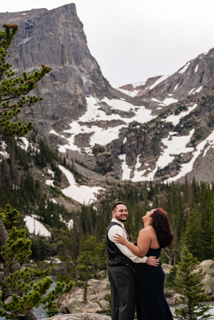 A newly engaged couple wearing a suit and gown snuggling up and laughing together in front of a beautiful mountain and Dream Lake. Photo by Gabby Jockers Photography. rmnp engagement photography, rmnp engagement photos, rmnp engagement session, rocky mountain national park engagement photos, rocky mountain national park engagement session, rocky mountain national park photography, waterfall engagement photos, dream lake engagement photos, waterfall engagement session, hiking engagement, adventure photos, adventure session, couples photos