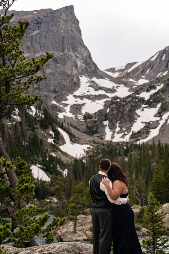A newly engaged couple wearing a suit and gown snuggling up and enjoying the view in front of a beautiful mountain and Dream Lake. Photo by Gabby Jockers Photography. rmnp engagement photography, rmnp engagement photos, rmnp engagement session, rocky mountain national park engagement photos, rocky mountain national park engagement session, rocky mountain national park photography, waterfall engagement photos, dream lake engagement photos, waterfall engagement session, hiking engagement, adventure photos, adventure session, couples photos