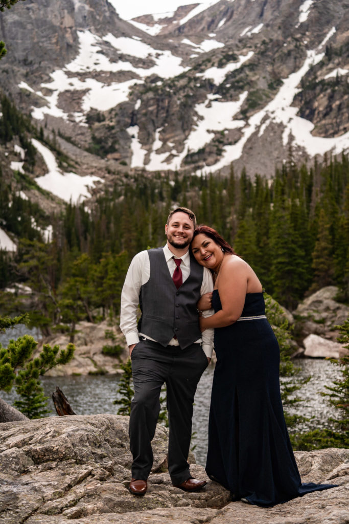 A newly engaged couple wearing a suit and gown snuggling up in front of a beautiful mountain and Dream Lake. Photo by Gabby Jockers Photography. rmnp engagement photography, rmnp engagement photos, rmnp engagement session, rocky mountain national park engagement photos, rocky mountain national park engagement session, rocky mountain national park photography, waterfall engagement photos, dream lake engagement photos, waterfall engagement session, hiking engagement, adventure photos, adventure session, couples photos