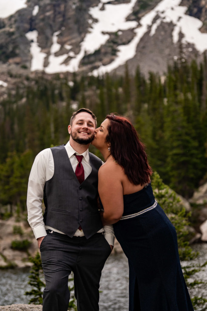 A woman kisses her fiance's cheek while he smiles in front of Dream lake. Photo by Gabby Jockers Photography. rmnp engagement photography, rmnp engagement photos, rmnp engagement session, rocky mountain national park engagement photos, rocky mountain national park engagement session, rocky mountain national park photography, waterfall engagement photos, dream lake engagement photos, waterfall engagement session, hiking engagement, adventure photos, adventure session, couples photos