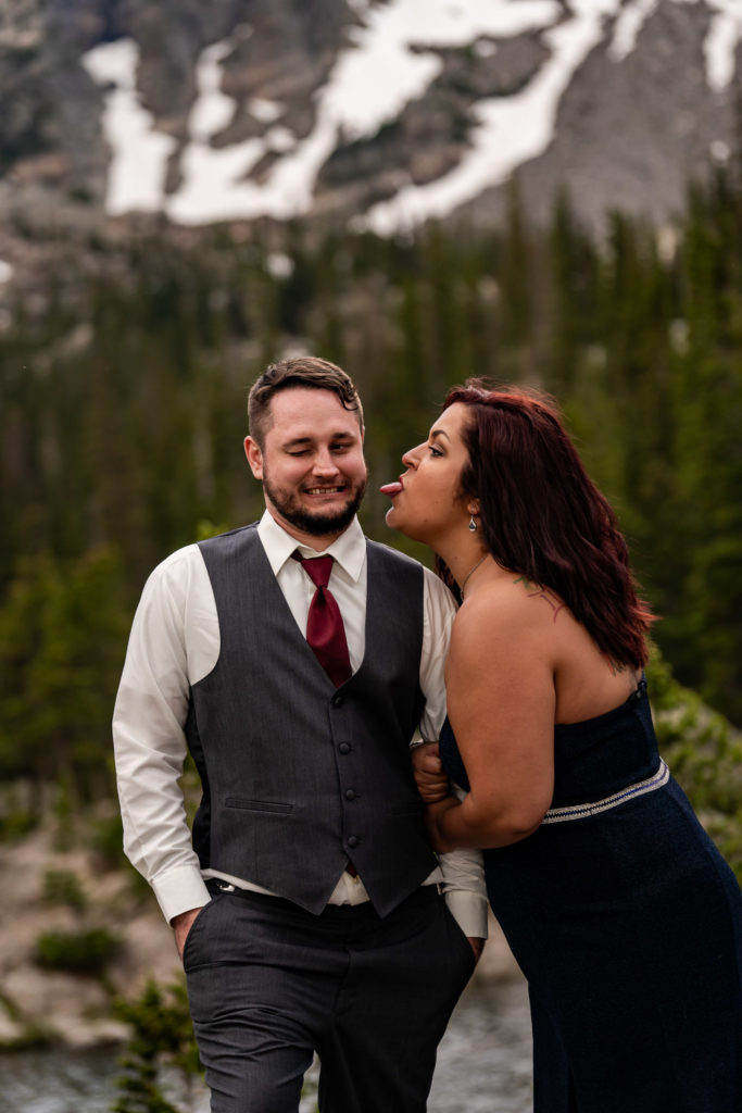 A woman sticking her tongue out at her fiance while he makes a funny face at Dream Lake. Photo by Gabby Jockers Photography. rmnp engagement photography, rmnp engagement photos, rmnp engagement session, rocky mountain national park engagement photos, rocky mountain national park engagement session, rocky mountain national park photography, waterfall engagement photos, dream lake engagement photos, waterfall engagement session, hiking engagement, adventure photos, adventure session, couples photos