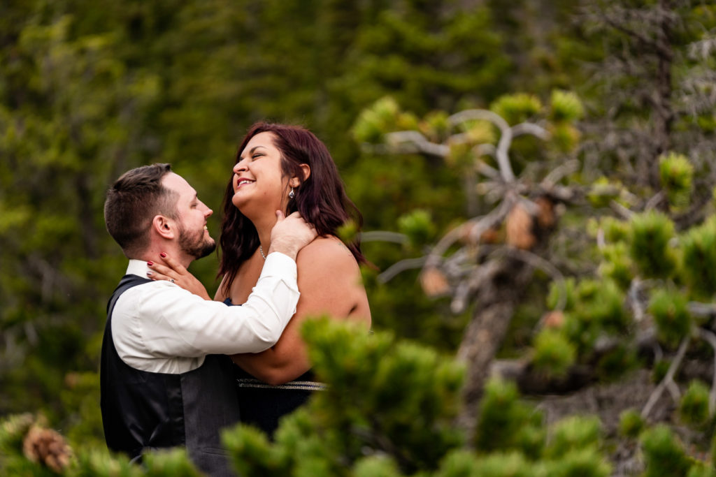 A man caresses his fiance's neck as they smile at each other at Dream Lake. Photo by Gabby Jockers Photography. rmnp engagement photography, rmnp engagement photos, rmnp engagement session, rocky mountain national park engagement photos, rocky mountain national park engagement session, rocky mountain national park photography, waterfall engagement photos, dream lake engagement photos, waterfall engagement session, hiking engagement, adventure photos, adventure session, couples photos
