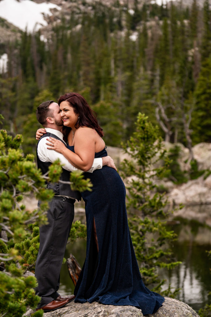 A newly engaged couple wearing a suit and gown snuggling up and laughing in front of a beautiful mountain and Dream Lake. Photo by Gabby Jockers Photography. rmnp engagement photography, rmnp engagement photos, rmnp engagement session, rocky mountain national park engagement photos, rocky mountain national park engagement session, rocky mountain national park photography, waterfall engagement photos, dream lake engagement photos, waterfall engagement session, hiking engagement, adventure photos, adventure session, couples photos