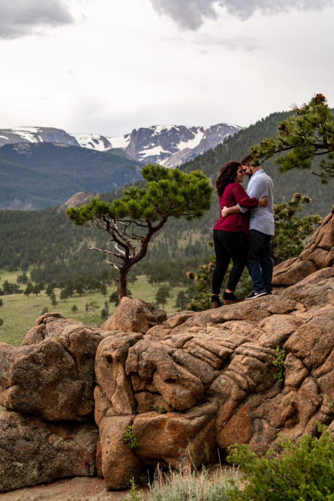 A man and woman embracing in front of big mountain views in the national park. Photo by Gabby Jockers Photography. rmnp engagement photography, rmnp engagement photos, rmnp engagement session, rocky mountain national park engagement photos, rocky mountain national park engagement session, rocky mountain national park photography, waterfall engagement photos, dream lake engagement photos, waterfall engagement session, hiking engagement, adventure photos, adventure session, couples photos