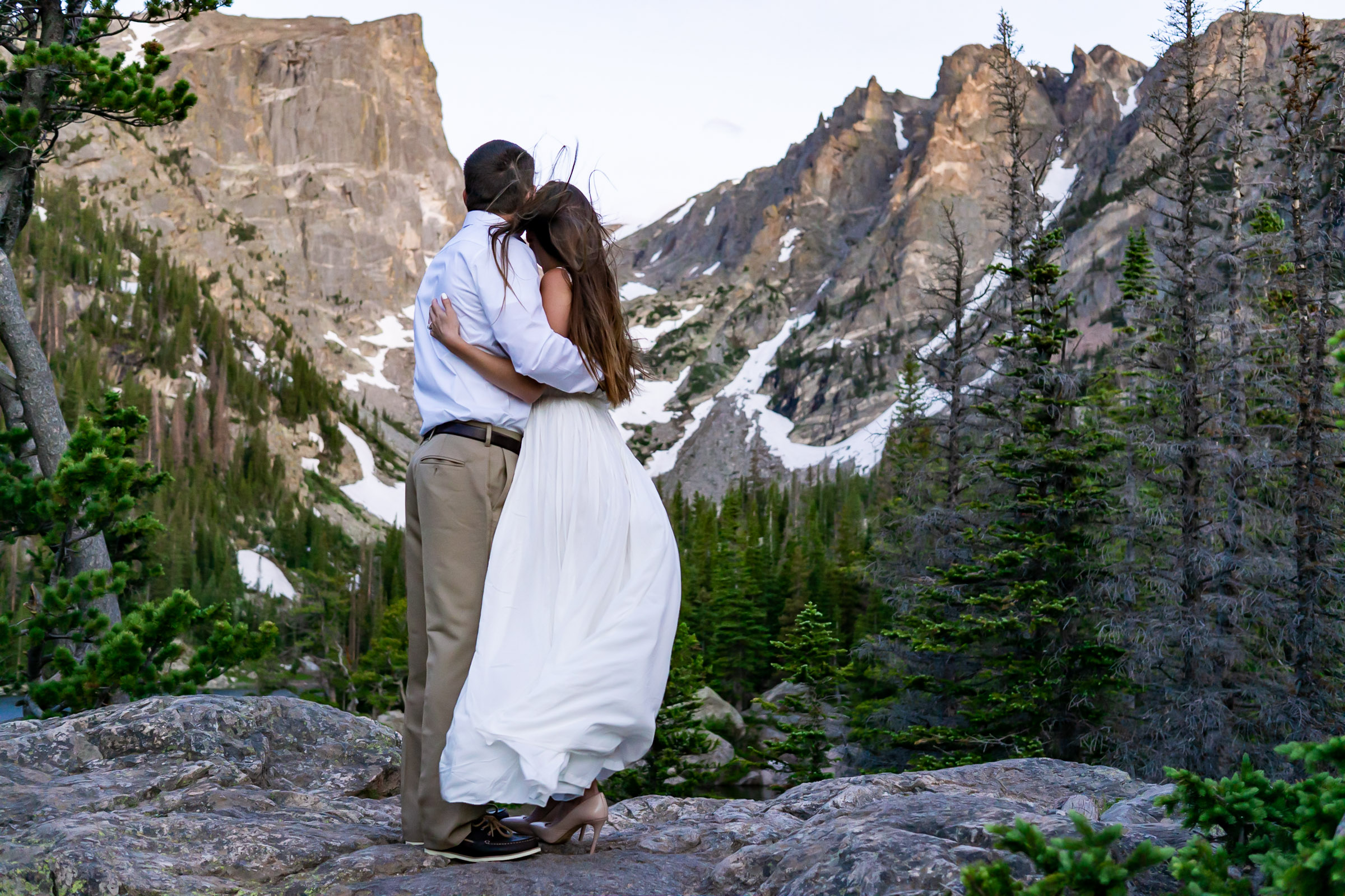 A couple holding each other in their arms and snuggling in the windy morning. Photo by Gabby Jockers Photography. Rocky mountain national park engagement photography, Rocky mountain national park engagement photos, Rocky mountain national park engagement session, RMNP elopement, dream lake engagement photos, dream lake engagement session, estes park engagement, estes park engagement photos, adventure photos, adventure session, couples photos