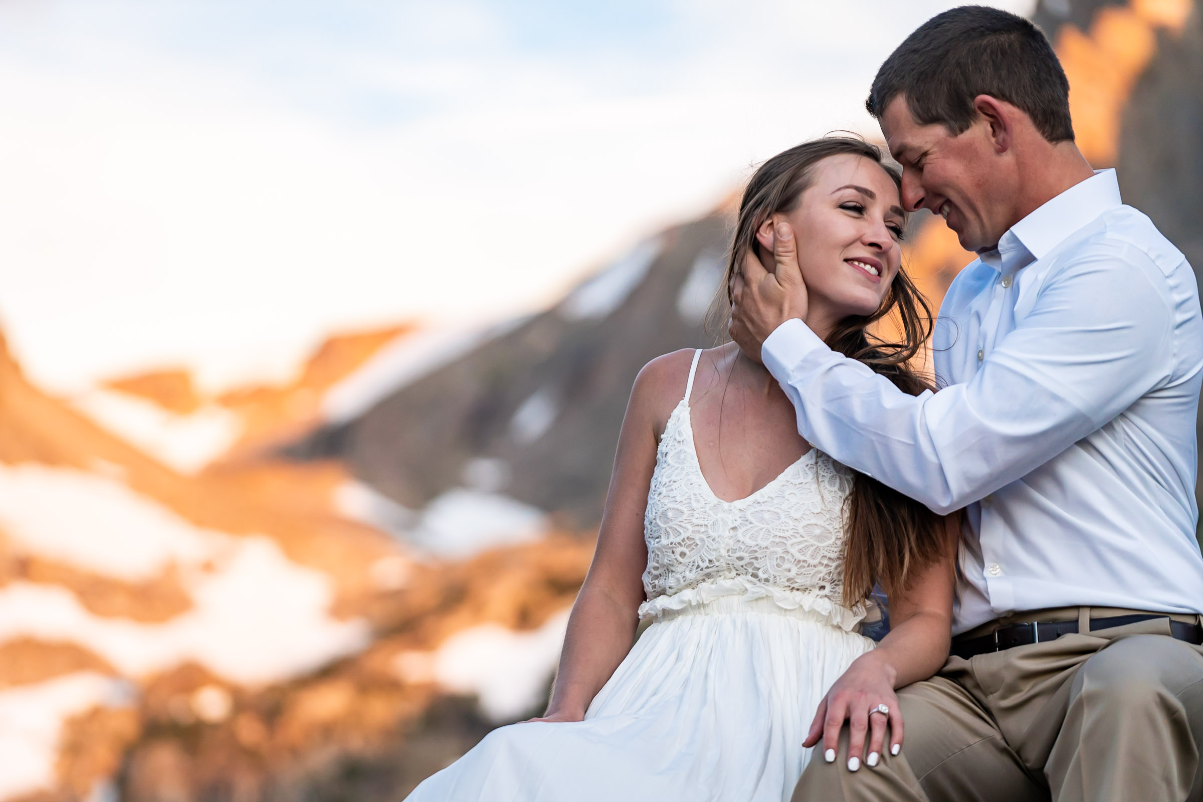A man and woman are seated, he holds her face gently while she smiles, the brilliant alpineglow lighting up the mountain behind them. Photo by Gabby Jockers Photography. Rocky mountain national park engagement photography, Rocky mountain national park engagement photos, Rocky mountain national park engagement session, RMNP elopement, dream lake engagement photos, dream lake engagement session, estes park engagement, estes park engagement photos, adventure photos, adventure session, couples photos