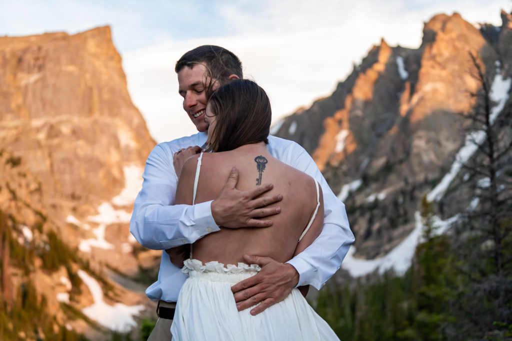 A man is hugging his fiance tight with a huge smile on his face in front of a sharp mountain lit by the rising sun. Photo by Gabby Jockers Photography. Rocky mountain national park engagement photography, Rocky mountain national park engagement photos, Rocky mountain national park engagement session, RMNP elopement, dream lake engagement photos, dream lake engagement session, estes park engagement, estes park engagement photos, adventure photos, adventure session, couples photos