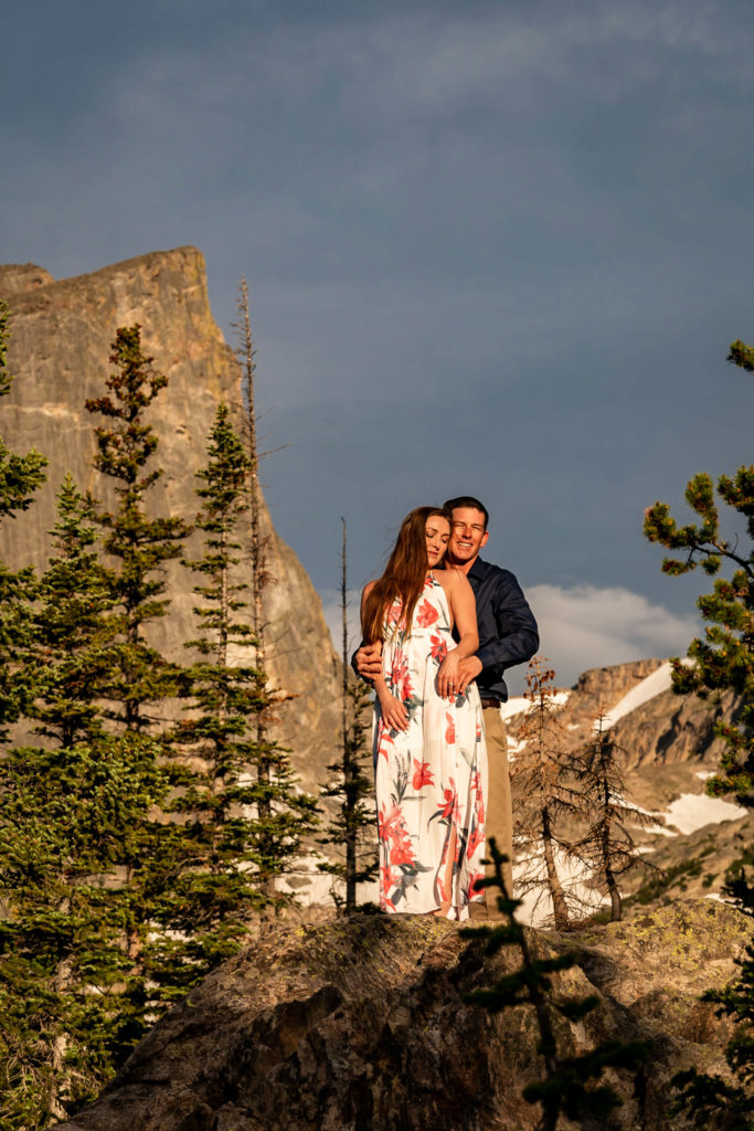 A man and woman facing the bright morning sun in front of a sharp, tall mountain. Photo by Gabby Jockers Photography. Rocky mountain national park engagement photography, Rocky mountain national park engagement photos, Rocky mountain national park engagement session, RMNP elopement, dream lake engagement photos, dream lake engagement session, estes park engagement, estes park engagement photos, adventure photos, adventure session, couples photos