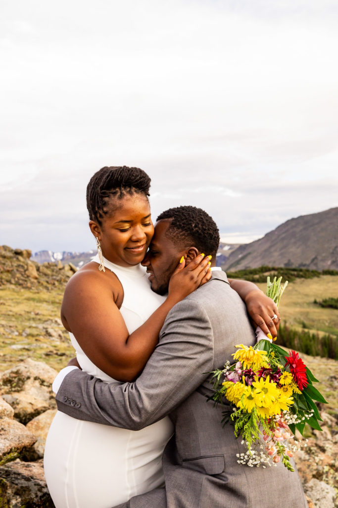 A man and woman in wedding clothes and a wildflower bouquet cuddling with each other in front of a beautiful mountain vista. Photo by Gabby Jockers Photography. Rocky Mountain National Park elopement photography, Rocky Mountain National Park elopement photos, Rocky Mountain National Park elopement, Colorado elopement ideas, Colorado elopement inspiration, elopement ideas, elopement photography, mountain elopement, national park elopement, outdoor elopement, adventure elopement, Black couple, Black elopement, Black wedding