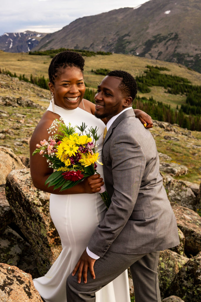 A man and woman in wedding clothes and a wildflower bouquet chatting with each other in front of a beautiful mountain vista. Photo by Gabby Jockers Photography. Rocky Mountain National Park elopement photography, Rocky Mountain National Park elopement photos, Rocky Mountain National Park elopement, Colorado elopement ideas, Colorado elopement inspiration, elopement ideas, elopement photography, mountain elopement, national park elopement, outdoor elopement, adventure elopement, Black couple, Black elopement, Black wedding