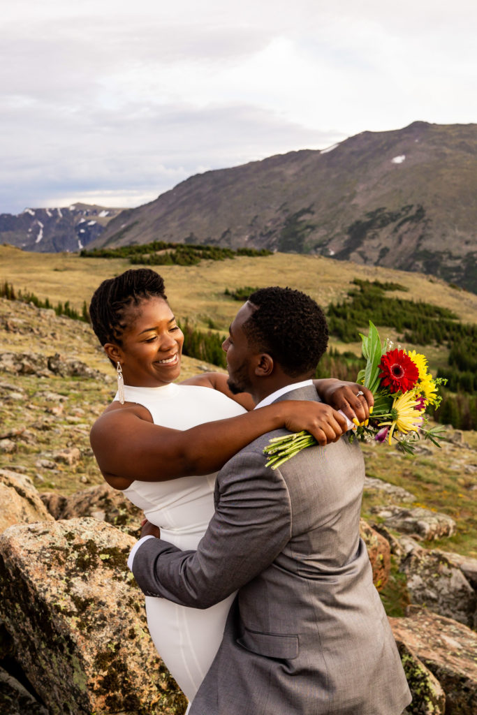 A couple in wedding clothes with their arms wrapped around each other, smiling at each other in front of the mountains. Photo by Gabby Jockers Photography. Rocky Mountain National Park elopement photography, Rocky Mountain National Park elopement photos, Rocky Mountain National Park elopement, Colorado elopement ideas, Colorado elopement inspiration, elopement ideas, elopement photography, mountain elopement, national park elopement, outdoor elopement, adventure elopement, Black couple, Black elopement, Black wedding
