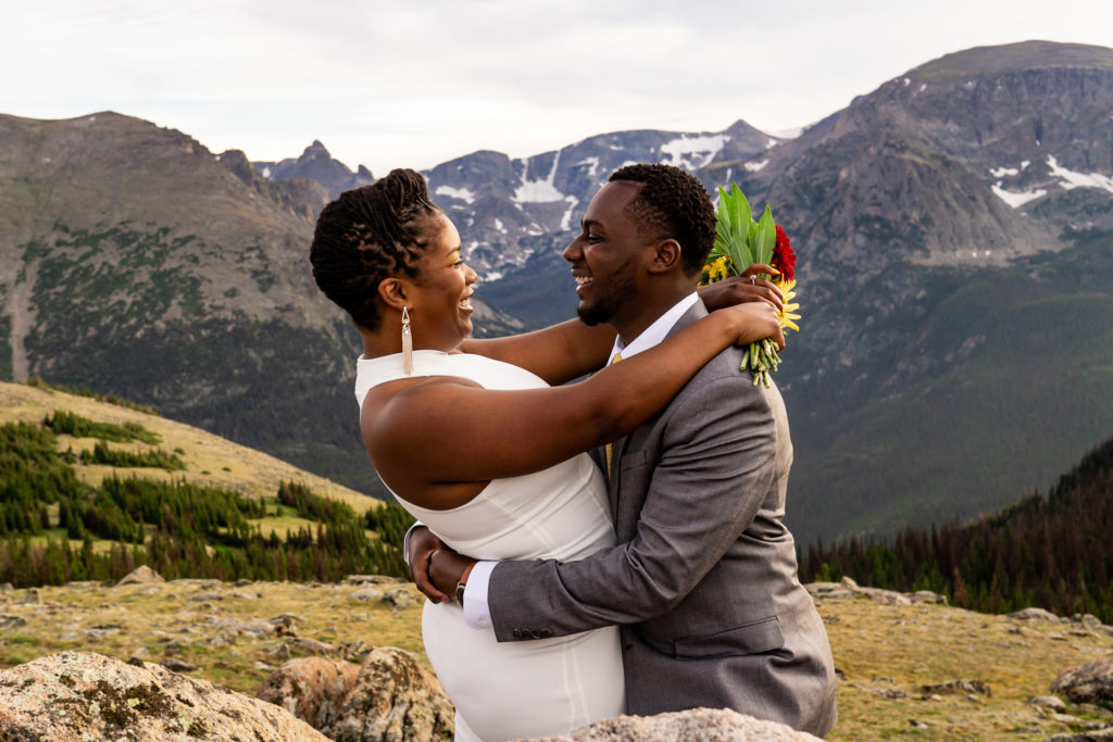 A couple in wedding clothes with their arms wrapped around each other, smiling at each other. Photo by Gabby Jockers Photography. Rocky Mountain National Park elopement photography, Rocky Mountain National Park elopement photos, Rocky Mountain National Park elopement, Colorado elopement ideas, Colorado elopement inspiration, elopement ideas, elopement photography, mountain elopement, national park elopement, outdoor elopement, adventure elopement, Black couple, Black elopement, Black wedding