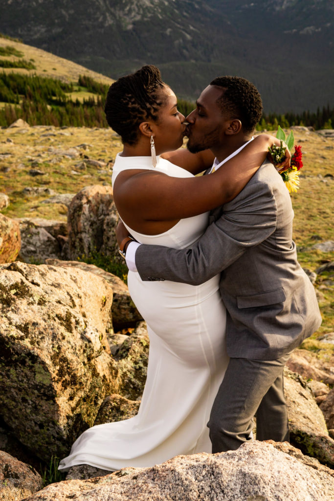 A couple in wedding clothes kissing passionately on top of a mountain. Photo by Gabby Jockers Photography. Rocky Mountain National Park elopement photography, Rocky Mountain National Park elopement photos, Rocky Mountain National Park elopement, Colorado elopement ideas, Colorado elopement inspiration, elopement ideas, elopement photography, mountain elopement, national park elopement, outdoor elopement, adventure elopement, Black couple, Black elopement, Black wedding