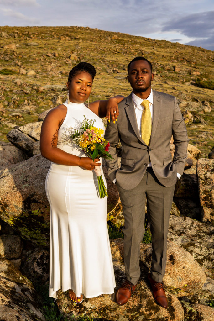 A couple in wedding clothes with a wildflower bouquet looking at the camera in a power stance. Photo by Gabby Jockers Photography. Rocky Mountain National Park elopement photography, Rocky Mountain National Park elopement photos, Rocky Mountain National Park elopement, Colorado elopement ideas, Colorado elopement inspiration, elopement ideas, elopement photography, mountain elopement, national park elopement, outdoor elopement, adventure elopement, Black couple, Black elopement, Black wedding