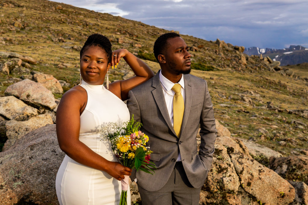 A couple in wedding clothes standing elegantly, the woman looking over her shoulder and holding her bouquet while her man stares in the other direction. Photo by Gabby Jockers Photography. Rocky Mountain National Park elopement photography, Rocky Mountain National Park elopement photos, Rocky Mountain National Park elopement, Colorado elopement ideas, Colorado elopement inspiration, elopement ideas, elopement photography, mountain elopement, national park elopement, outdoor elopement, adventure elopement, Black couple, Black elopement, Black wedding