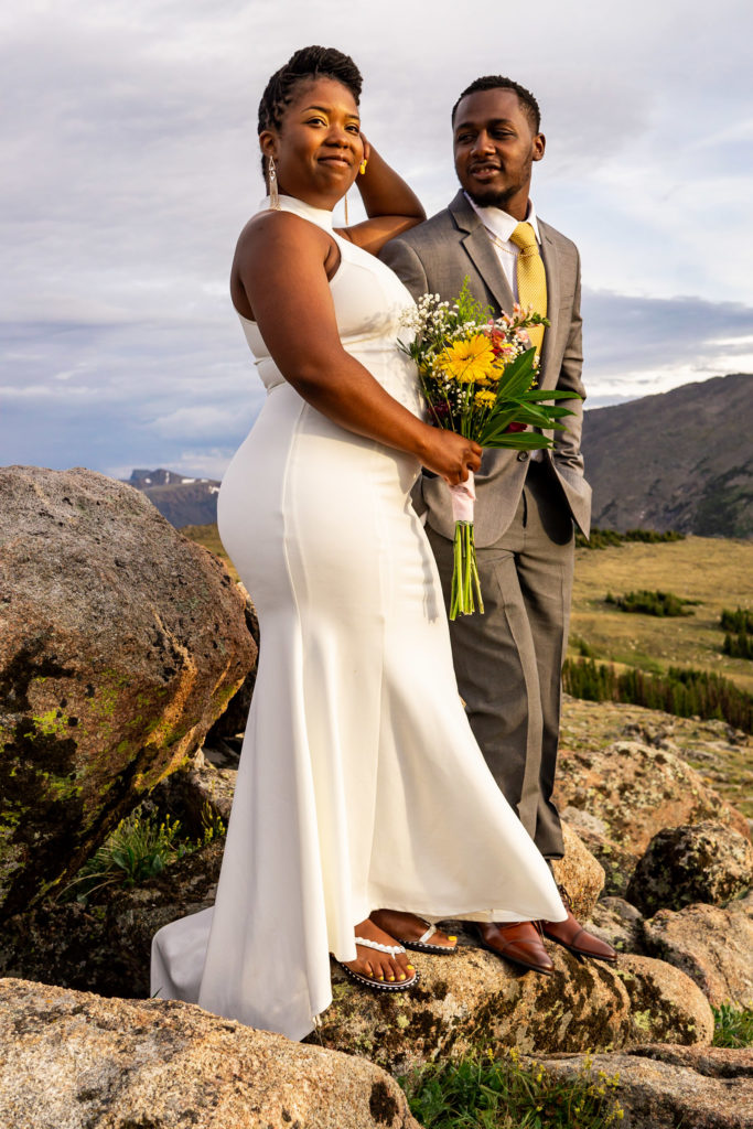 A couple in wedding clothes standing elegantly, the woman looking over her shoulder and holding her bouquet while her man stares lovingly at her. Photo by Gabby Jockers Photography. Rocky Mountain National Park elopement photography, Rocky Mountain National Park elopement photos, Rocky Mountain National Park elopement, Colorado elopement ideas, Colorado elopement inspiration, elopement ideas, elopement photography, mountain elopement, national park elopement, outdoor elopement, adventure elopement, Black couple, Black elopement, Black wedding