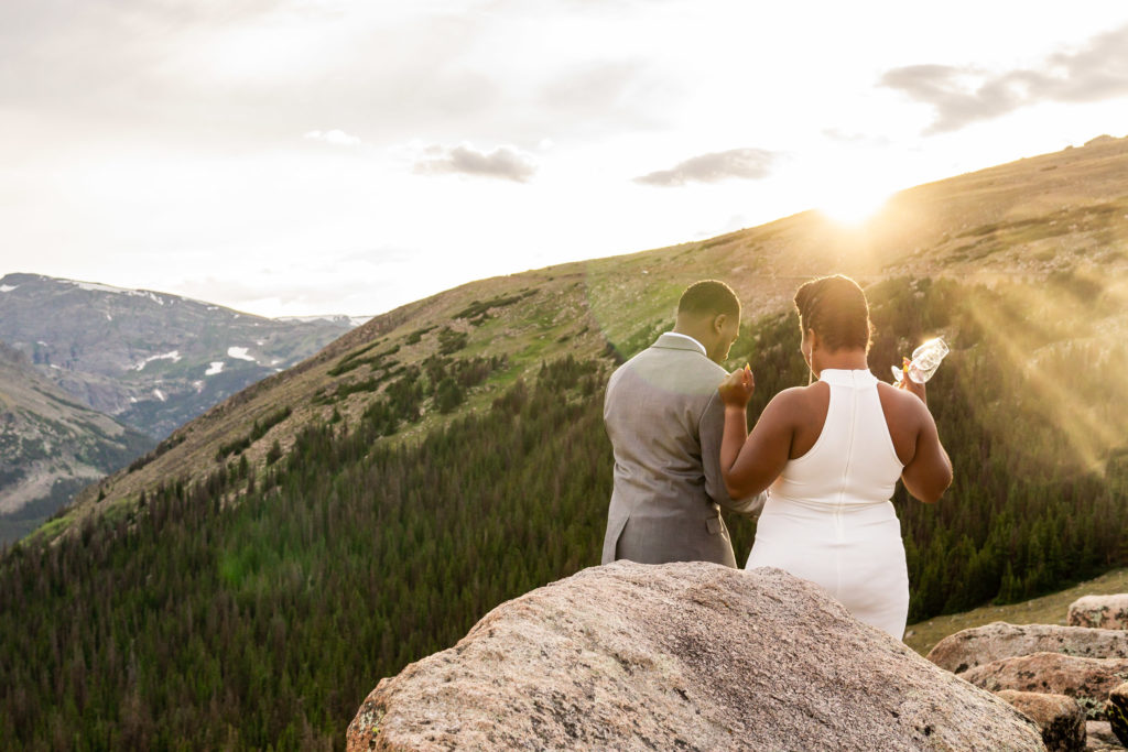 A couple in wedding clothes getting ready to pop a bottle of champagne for celebration! Photo by Gabby Jockers Photography. Rocky Mountain National Park elopement photography, Rocky Mountain National Park elopement photos, Rocky Mountain National Park elopement, Colorado elopement ideas, Colorado elopement inspiration, elopement ideas, elopement photography, mountain elopement, national park elopement, outdoor elopement, adventure elopement, Black couple, Black elopement, Black wedding
