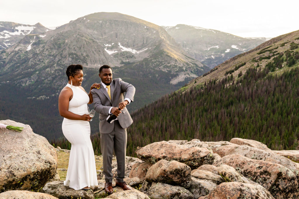 A couple in wedding clothes popping a bottle of champagne for celebration! Photo by Gabby Jockers Photography. Rocky Mountain National Park elopement photography, Rocky Mountain National Park elopement photos, Rocky Mountain National Park elopement, Colorado elopement ideas, Colorado elopement inspiration, elopement ideas, elopement photography, mountain elopement, national park elopement, outdoor elopement, adventure elopement, Black couple, Black elopement, Black wedding
