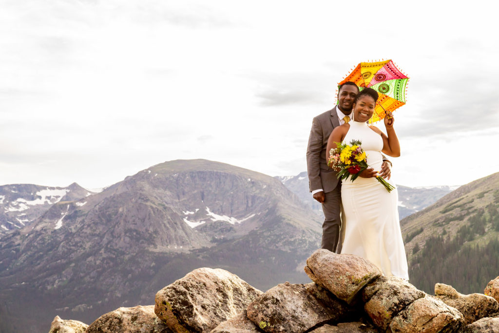 A man and woman in wedding clothes, with a wildflower bouquet and colorful parasol, standing in front of a big mountain view. Photo by Gabby Jockers Photography. Rocky Mountain National Park elopement photography, Rocky Mountain National Park elopement photos, Rocky Mountain National Park elopement, Colorado elopement ideas, Colorado elopement inspiration, elopement ideas, elopement photography, mountain elopement, national park elopement, outdoor elopement, adventure elopement, Black couple, Black elopement, Black wedding