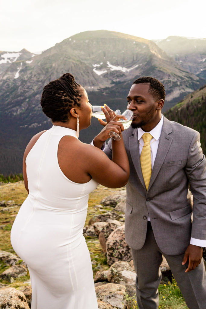 A couple in wedding clothes just popped a bottle of champagne and are taking their first sip together. Photo by Gabby Jockers Photography. Rocky Mountain National Park elopement photography, Rocky Mountain National Park elopement photos, Rocky Mountain National Park elopement, Colorado elopement ideas, Colorado elopement inspiration, elopement ideas, elopement photography, mountain elopement, national park elopement, outdoor elopement, adventure elopement, Black couple, Black elopement, Black wedding