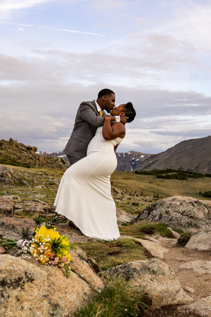 A woman in a wedding dress being dipped for a kiss by her fiance in a gray suit. Photo by Gabby Jockers Photography. Rocky Mountain National Park elopement photography, Rocky Mountain National Park elopement photos, Rocky Mountain National Park elopement, Colorado elopement ideas, Colorado elopement inspiration, elopement ideas, elopement photography, mountain elopement, national park elopement, outdoor elopement, adventure elopement, Black couple, Black elopement, Black wedding