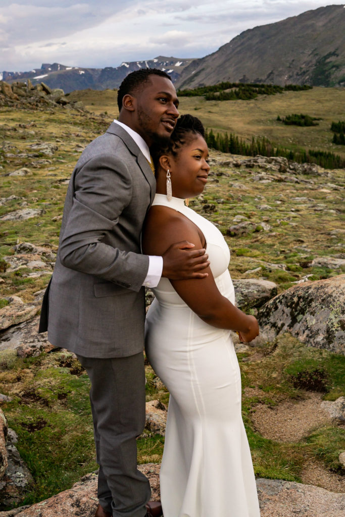 A man in a gray suit holding on to his bride-to-be wearing a white dress as they look at the mountains together. Photo by Gabby Jockers Photography. Rocky Mountain National Park elopement photography, Rocky Mountain National Park elopement photos, Rocky Mountain National Park elopement, Colorado elopement ideas, Colorado elopement inspiration, elopement ideas, elopement photography, mountain elopement, national park elopement, outdoor elopement, adventure elopement, Black couple, Black elopement, Black wedding