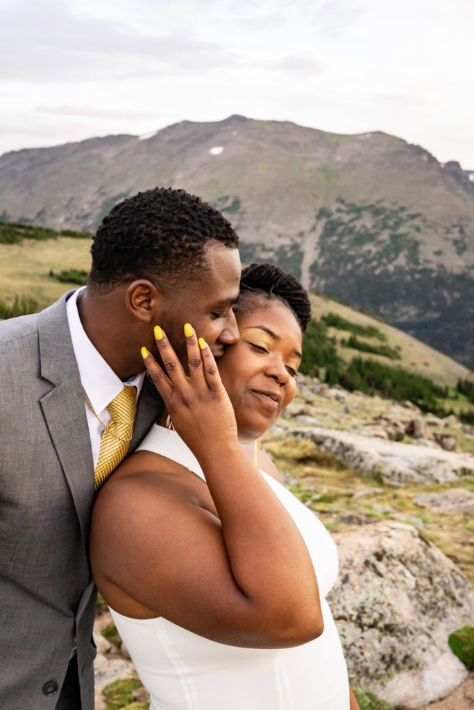 A man in a gray suit kisses his fiance on the cheek from behind as she smiles. Photo by Gabby Jockers Photography. Rocky Mountain National Park elopement photography, Rocky Mountain National Park elopement photos, Rocky Mountain National Park elopement, Colorado elopement ideas, Colorado elopement inspiration, elopement ideas, elopement photography, mountain elopement, national park elopement, outdoor elopement, adventure elopement, Black couple, Black elopement, Black wedding