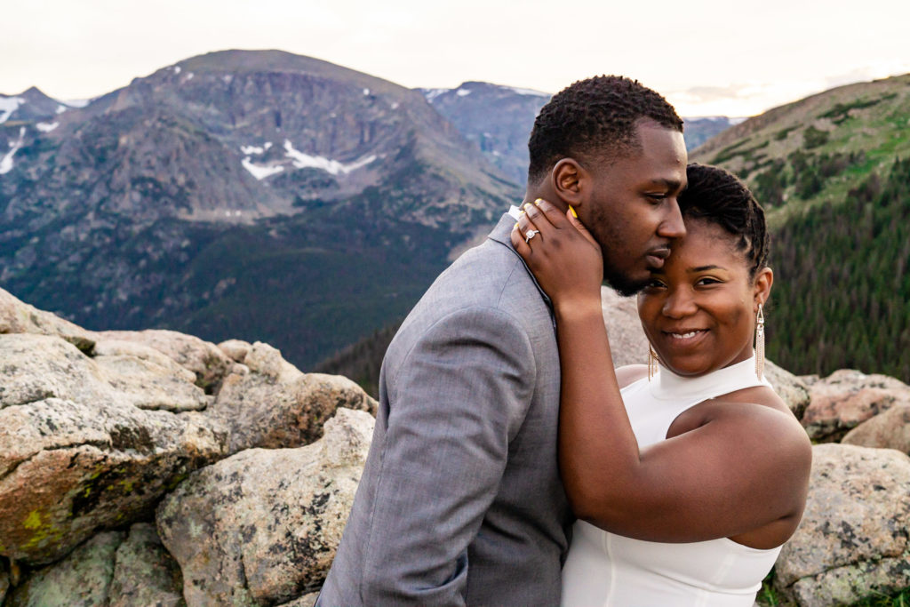 A woman in a wedding dress smiles at the camera while half facing her fiance in a gray suit. Photo by Gabby Jockers Photography. Rocky Mountain National Park elopement photography, Rocky Mountain National Park elopement photos, Rocky Mountain National Park elopement, Colorado elopement ideas, Colorado elopement inspiration, elopement ideas, elopement photography, mountain elopement, national park elopement, outdoor elopement, adventure elopement, Black couple, Black elopement, Black wedding