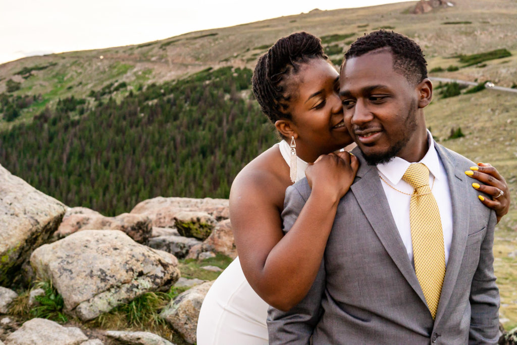 A woman in a wedding dress holds on to her fiance from behind and whispers into his ear. Photo by Gabby Jockers Photography. Rocky Mountain National Park elopement photography, Rocky Mountain National Park elopement photos, Rocky Mountain National Park elopement, Colorado elopement ideas, Colorado elopement inspiration, elopement ideas, elopement photography, mountain elopement, national park elopement, outdoor elopement, adventure elopement, Black couple, Black elopement, Black wedding