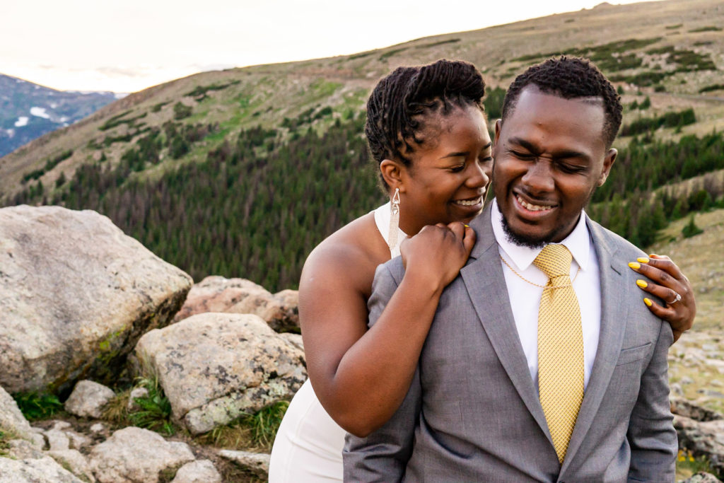 A woman in a wedding dress holds on to her fiance from behind as they laugh together. Photo by Gabby Jockers Photography. Rocky Mountain National Park elopement photography, Rocky Mountain National Park elopement photos, Rocky Mountain National Park elopement, Colorado elopement ideas, Colorado elopement inspiration, elopement ideas, elopement photography, mountain elopement, national park elopement, outdoor elopement, adventure elopement, Black couple, Black elopement, Black wedding