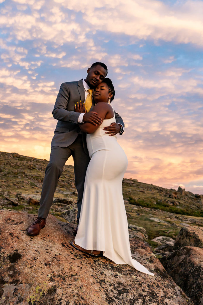 A couple in wedding clothes in a comfortable embrace in front of a colorful, cloudy sunset. Photo by Gabby Jockers Photography. Rocky Mountain National Park elopement photography, Rocky Mountain National Park elopement photos, Rocky Mountain National Park elopement, Colorado elopement ideas, Colorado elopement inspiration, elopement ideas, elopement photography, mountain elopement, national park elopement, outdoor elopement, adventure elopement, Black couple, Black elopement, Black wedding