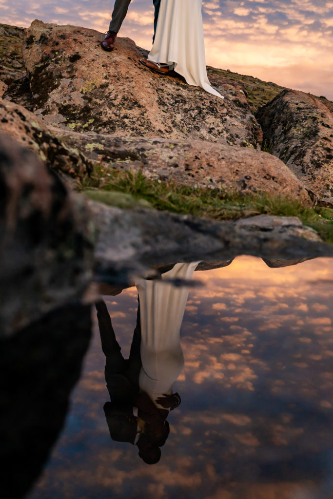 The reflection of a couple in wedding clothes during a colorful sunset. Photo by Gabby Jockers Photography. Rocky Mountain National Park elopement photography, Rocky Mountain National Park elopement photos, Rocky Mountain National Park elopement, Colorado elopement ideas, Colorado elopement inspiration, elopement ideas, elopement photography, mountain elopement, national park elopement, outdoor elopement, adventure elopement, Black couple, Black elopement, Black wedding