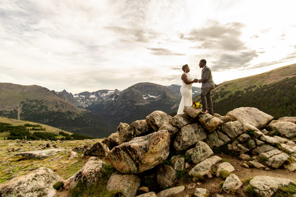 A man and woman in wedding clothes, with a wildflower bouquet, standing in front of a big mountain view. Photo by Gabby Jockers Photography. Rocky Mountain National Park elopement photography, Rocky Mountain National Park elopement photos, Rocky Mountain National Park elopement, Colorado elopement ideas, Colorado elopement inspiration, elopement ideas, elopement photography, mountain elopement, national park elopement, outdoor elopement, adventure elopement, Black couple, Black elopement, Black wedding
