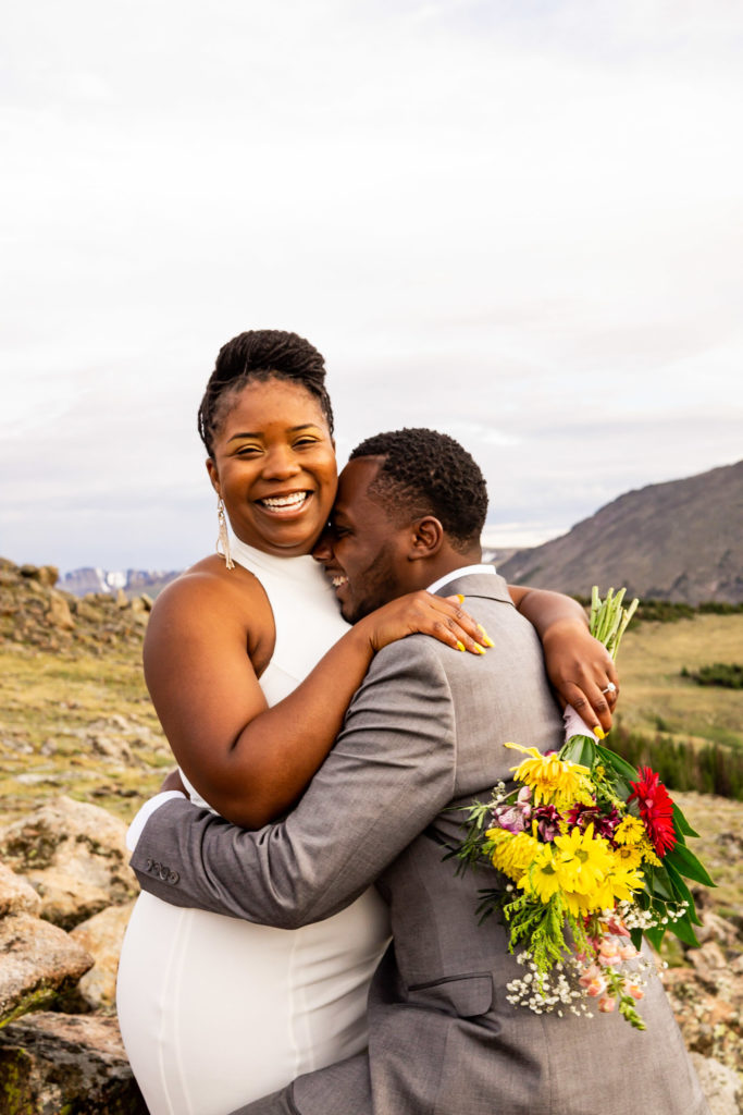 A man and woman in wedding clothes and a wildflower bouquet laughing with each other in front of a beautiful mountain vista. Photo by Gabby Jockers Photography. Rocky Mountain National Park elopement photography, Rocky Mountain National Park elopement photos, Rocky Mountain National Park elopement, Colorado elopement ideas, Colorado elopement inspiration, elopement ideas, elopement photography, mountain elopement, national park elopement, outdoor elopement, adventure elopement, Black couple, Black elopement, Black wedding