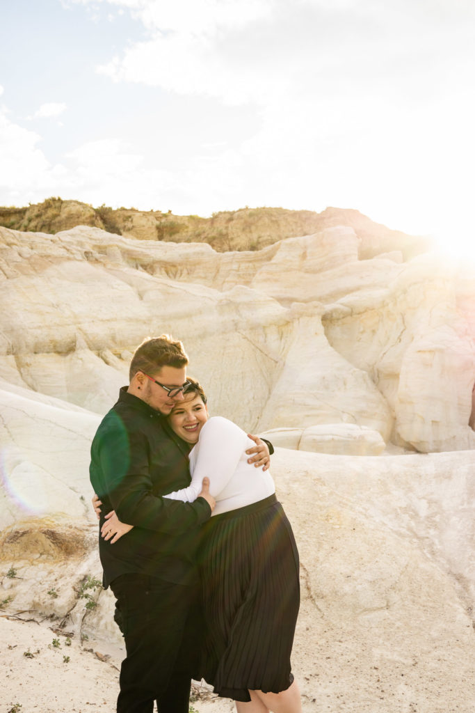 A couple happy and smiling, hugging each other hard, in front of the brightly shining sun. Photo by Gabby Jockers Photography. Paint mines engagement photography, Paint mines engagement photos, Paint mines engagement session, colorado springs engagement photos, colorado springs engagement session, colorado engagement photos, colorado engagement session, hiking engagement, adventure photos, adventure session, couples photos, paint mines colorado, paint mines calhan, paint mines elopement, colorado elopement