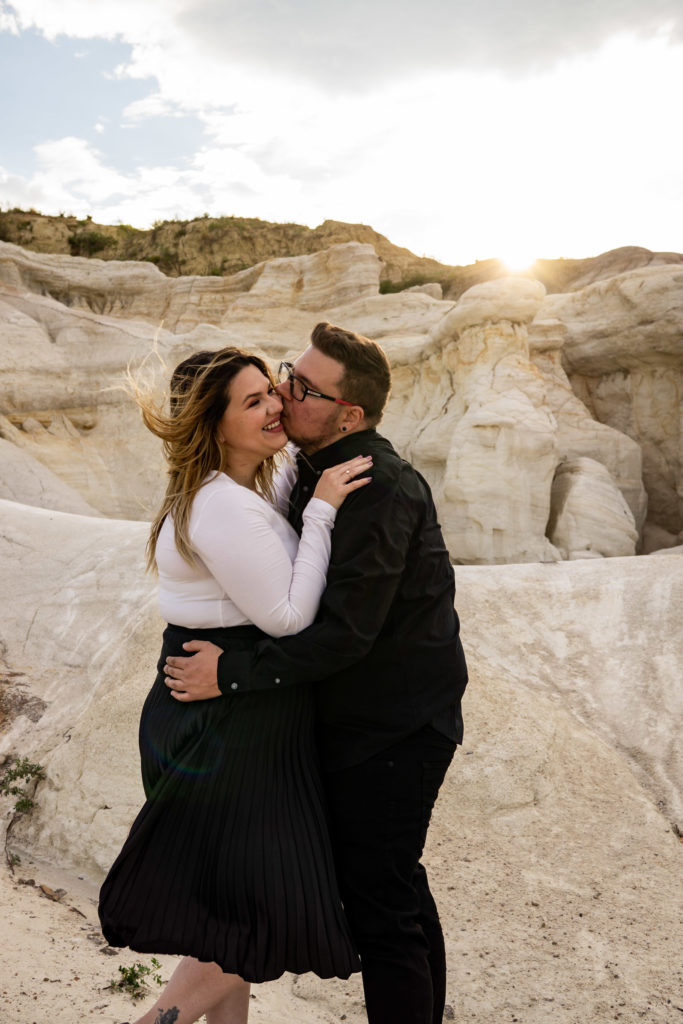 A man kisses his fiance's cheek while she smiles as they're standing among white stones in the Paint Mines. Photo by Gabby Jockers Photography. Paint mines engagement photography, Paint mines engagement photos, Paint mines engagement session, colorado springs engagement photos, colorado springs engagement session, colorado engagement photos, colorado engagement session, hiking engagement, adventure photos, adventure session, couples photos, paint mines colorado, paint mines calhan, paint mines elopement, colorado elopement