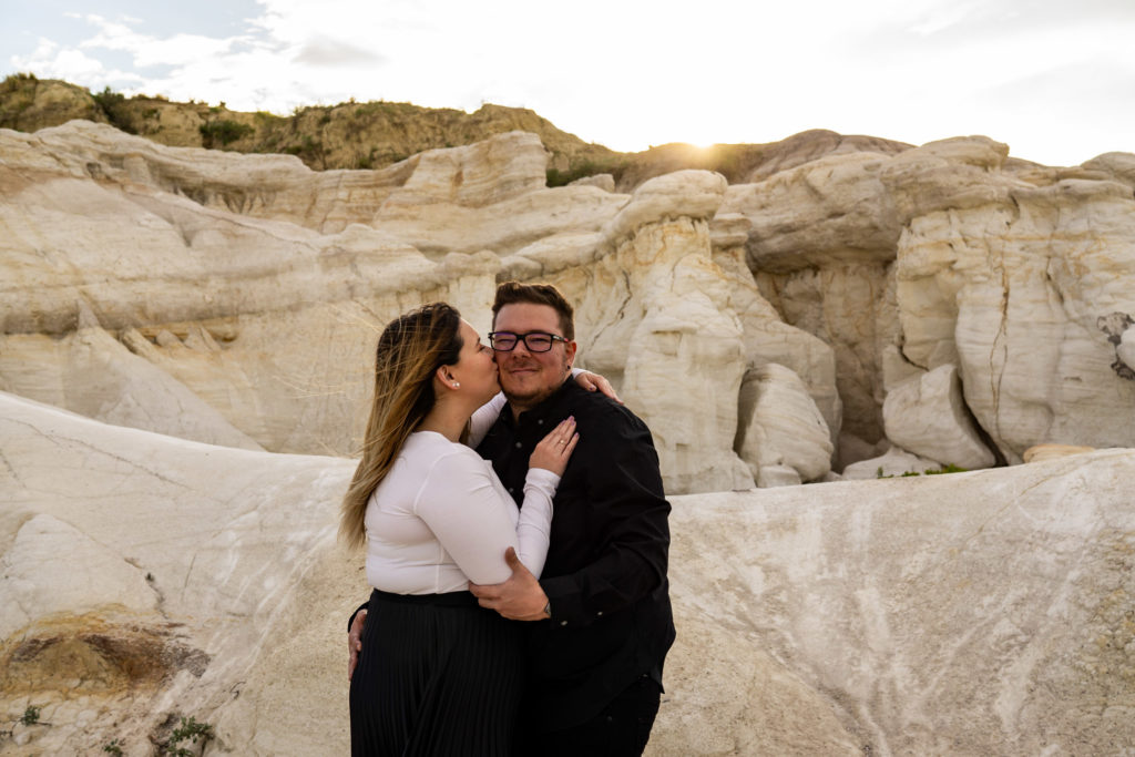 A woman kisses her fiance's cheek while he smiles as they're standing among white stones in the Paint Mines. Photo by Gabby Jockers Photography. Paint mines engagement photography, Paint mines engagement photos, Paint mines engagement session, colorado springs engagement photos, colorado springs engagement session, colorado engagement photos, colorado engagement session, hiking engagement, adventure photos, adventure session, couples photos, paint mines colorado, paint mines calhan, paint mines elopement, colorado elopement