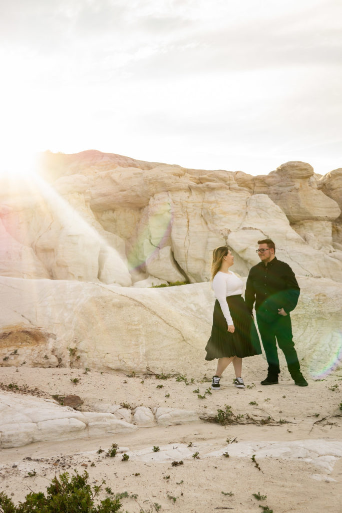 A couple holds hands and stand together in the middle of the white stone Paint Mines with the sun shining brightly. Photo by Gabby Jockers Photography. Paint mines engagement photography, Paint mines engagement photos, Paint mines engagement session, colorado springs engagement photos, colorado springs engagement session, colorado engagement photos, colorado engagement session, hiking engagement, adventure photos, adventure session, couples photos, paint mines colorado, paint mines calhan, paint mines elopement, colorado elopement