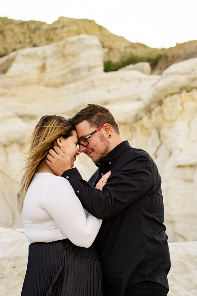 A man runs his hands through his fiance's hair as they stand face to face smiling. Photo by Gabby Jockers Photography. Paint mines engagement photography, Paint mines engagement photos, Paint mines engagement session, colorado springs engagement photos, colorado springs engagement session, colorado engagement photos, colorado engagement session, hiking engagement, adventure photos, adventure session, couples photos, paint mines colorado, paint mines calhan, paint mines elopement, colorado elopement