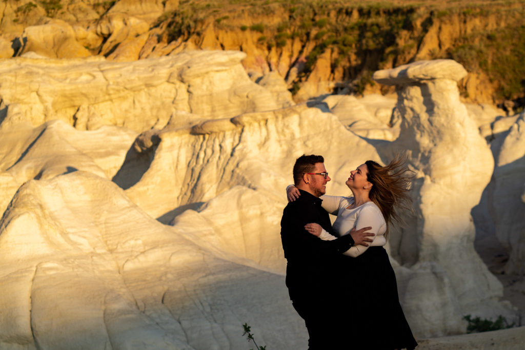 Newly engaged couple going in for a kiss in front of the white rocks and bright sunset light at the Calhan Paint Mines. Photo by Gabby Jockers Photography. Paint mines engagement photography, Paint mines engagement photos, Paint mines engagement session, colorado springs engagement photos, colorado springs engagement session, colorado engagement photos, colorado engagement session, hiking engagement, adventure photos, adventure session, couples photos, paint mines colorado, paint mines calhan, paint mines elopement, colorado elopement